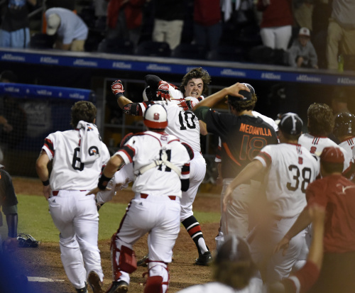 Preston Palmeiro is mobbed by his teammates after scoring the winning run in the bottom of the 12th.